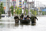 Japan Self Defense Force members rescue residents on a boat on a flooded road hit by heavy rain in Omuta, Fukuoka prefecture, southern Japan Tuesday, July 7, 2020. Rescue operations continued and rain threatened wider areas of the main island of Kyushu. (Juntaro Yokoyama/Kyodo News via AP)
