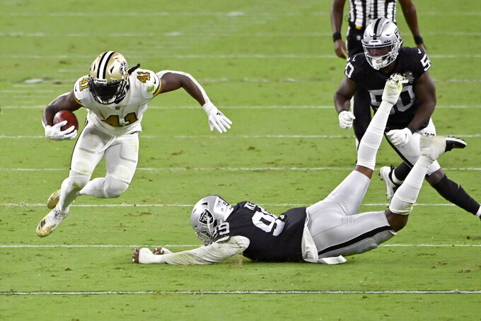 New Orleans Saints running back Alvin Kamara (41) avoids a tackle by Las Vegas Raiders defensive end Arden Key (99) during the second half of an NFL football game, Monday, Sept. 21, 2020, in Las Vegas. (AP Photo/David Becker)