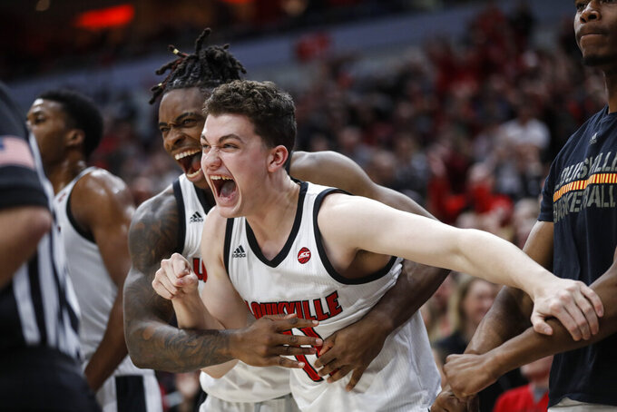 Louisville forward Quinn Slazinski (11) and forward Aidan Igiehon (22) react to a dunk during the second half of the team's NCAA college basketball game against Wake Forest on Wednesday, Feb. 5, 2020, in Louisville, Ky. Louisville won 86-76. (AP Photo/Wade Payne)