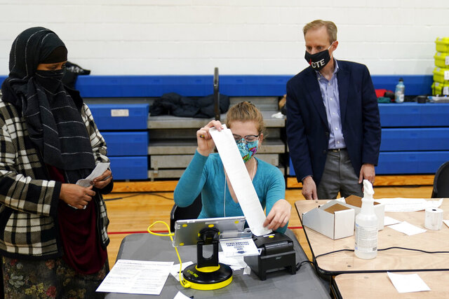 Minnesota Secretary of State Steve Simon visits with poll workers as he toured the Brian Coyle Center, on Election Day Tuesday, Nov. 3, 2020, in Minneapolis. (AP Photo/Jim Mone)