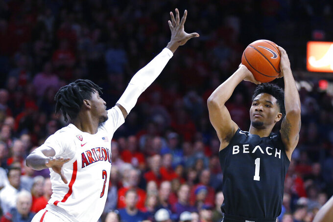 Long Beach State guard Michael Carter III (1) shoots over Arizona guard Dylan Smith in the first half during an NCAA college basketball game, Sunday, Nov. 24, 2019, in Tucson, Ariz. (AP Photo/Rick Scuteri)