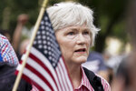 """A person stands as the national anthem plays during a rally near the U.S. Capitol in Washington, Saturday, Sept. 18, 2021. The rally was planned by allies of former President Donald Trump and aimed at supporting the so-called """"political prisoners"""" of the Jan. 6 insurrection at the U.S. Capitol. (AP Photo/Brynn Anderson)"""