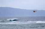 In this March 31, 2020 file photo a fire and rescue helicopter flies over a group of surfers on Oahu's North Shore near Haleiwa, Hawaii. Former Hawaii television reporter Angela Keen knows how to track people down. During the coronavirus pandemic, she's putting her people-finding skills to use as one of the original members of a Facebook group that has grown to more than 2,000 people called