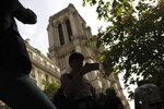 People take photographs next to the towers of the Notre Dame Cathedral in Paris, Sunday, April 21, 2019. The fire that engulfed Notre Dame during Holy Week forced worshippers to find other places to attend Easter services, and the Paris diocese invited them to join Sunday's Mass at the grandiose Saint-Eustache Church on the Right Bank of the Seine River. (AP Photo/Francisco Seco)