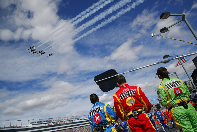 Kyle Busch's crew members watch the Thunderbirds fly over before a NASCAR Cup Series auto race at Las Vegas Motor Speedway, Sunday, March 3, 2019, in Las Vegas. (AP Photo/John Locher)