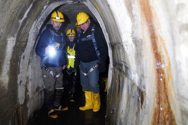 Danny Rohloff, construction management coordinator, shows Minneapolis Director of Public Works Robin Hutcheson and Gov. Tim Walz around a storm tunnel beneath the ground during a tour of the system in northeast Minneapolis on Friday, Jan. 10, 2020. (Anthony Souffle/Star Tribune via AP)