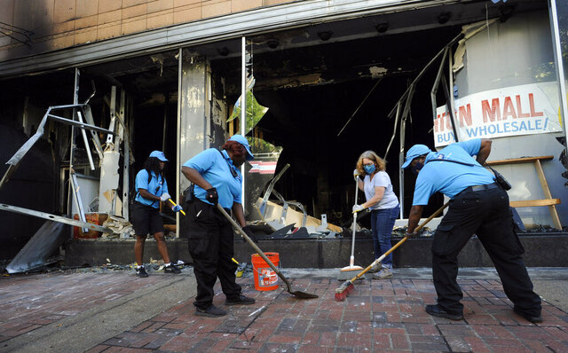 Workers and a volunteer clean up damage outside a burned-out clothing store in Birmingham, Ala., on Monday, June 1, 2020, following a night of unrest. People shattered windows, set fires and damaged monuments in a downtown park after a protest against the death of George Floyd. Floyd died after being restrained by Minneapolis police officers on May 25.  (AP Photo/Jay Reeves)