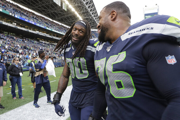 Seattle Seahawks defensive end Jadeveon Clowney, left, talks with teammate Duane Brown, right, after they defeated the Cincinnati Bengals in an NFL football game, Sunday, Sept. 8, 2019, in Seattle. (AP Photo/John Froschauer)