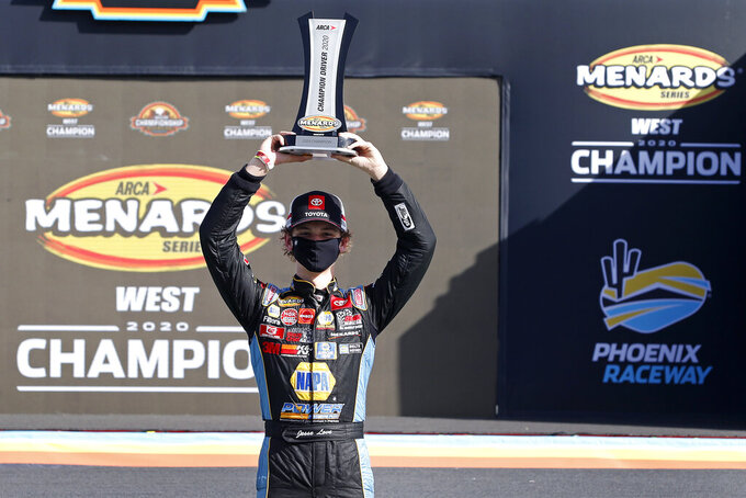 Jesse Love holds up the season championship trophy in Victory Lane following the ARCA Series auto race at Phoenix Raceway, Saturday, Nov. 7, 2020, in Avondale, Ariz. (AP Photo/Ralph Freso)
