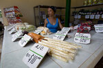 Roxana Lopez sell vegetables at a stall in Havana, Cuba, Wednesday, July 31, 2019. The Cuban government is capping prices for food and beverages throughout the country in order to control the risk of inflation due to a state wage hike and stagnant productivity. (AP Photo/Ismael Francisco)