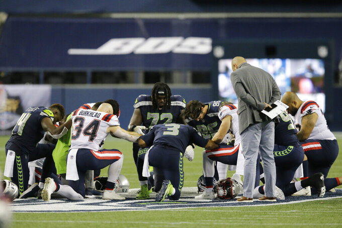 Seattle Seahawks quarterback Russell Wilson (3) prays with teammates and New England Patriots players after an NFL football game, Sunday, Sept. 20, 2020, in Seattle. The Seahawks won 35-30. (AP Photo/John Froschauer)