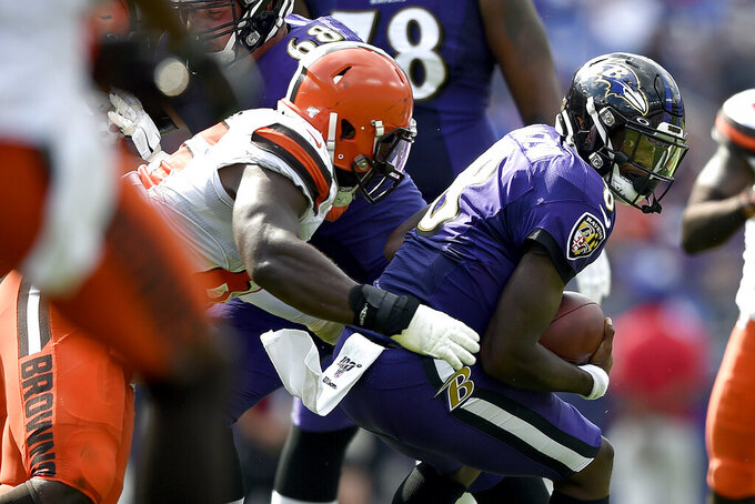 Baltimore Ravens quarterback Lamar Jackson, right, is tackled by Cleveland Browns defensive tackle Larry Ogunjobi during the second half of an NFL football game Sunday, Sept. 29, 2019, in Baltimore. (AP Photo/Gail Burton)