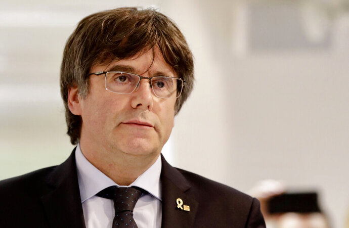 FILE - In this Monday, Oct. 14, 2019 file photo, former Catalan leader Carles Puigdemont arrives for a media conference in Brussels. Puigdemont's office said Friday Oct. 18, 2019, fugitive former Catalan leader Carles Puigdemont has handed himself in to Belgian justice authorities after Spain issued a new warrant for his arrest following the sentencing of 12 of his former colleagues. (AP Photo/Olivier Matthys, File)