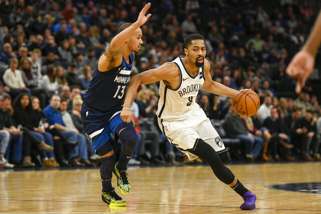 Brooklyn Nets guard Spencer Dinwiddie, right, drives past Minnesota Timberwolves guard Shabazz Napierduring the first half of an NBA basketball game Monday, Dec. 30, 2019, in Minneapolis. (AP Photo/Craig Lassig)