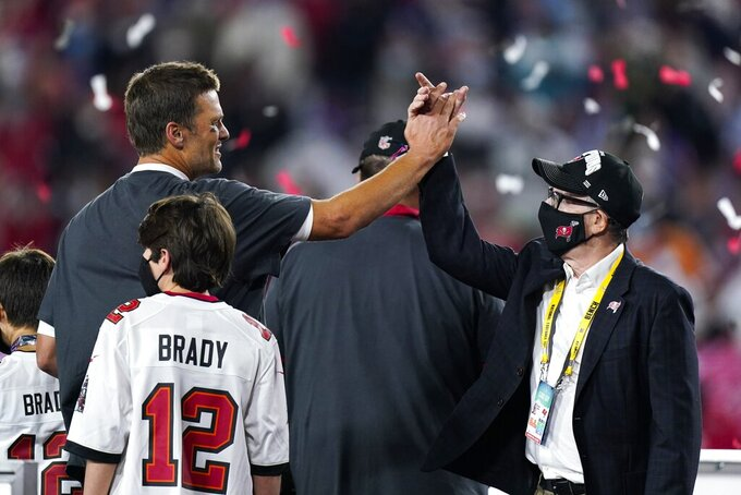 Tampa Bay Buccaneers quarterback Tom Brady celebrates with team owner Joel Glazer after the NFL Super Bowl 55 football game against the Kansas City Chiefs, Sunday, Feb. 7, 2021, in Tampa, Fla. The Buccaneers defeated the Chiefs 31-9 to win the Super Bowl. (AP Photo/Mark Humphrey)