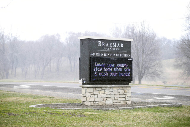 A brief shower passes by as a golf course sign highlights coronavirus preparedness Thursday, April 9, 2020, in Edina, Minn. Golf courses in Minnesota must remain closed until May 4 as part of the governor's extended stay-at-home order. (AP Photo/Jim Mone)