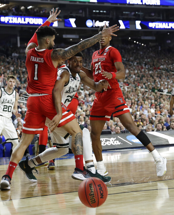 Michigan State forward Xavier Tillman, center, passes between Texas Tech's Brandone Francis, left, and Jarrett Culver, right, during the first half in the semifinals of the Final Four NCAA college basketball tournament, Saturday, April 6, 2019, in Minneapolis. (AP Photo/David J. Phillip)