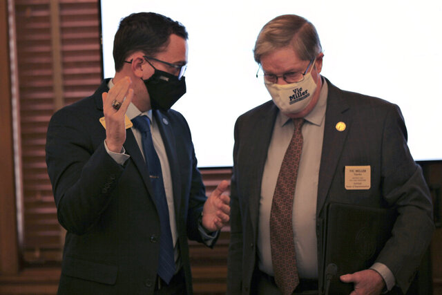 Kansas state Rep. Blake Carpenter, left, R-Derby, talks to Rep. Vic Miller, D-Topeka, after a House committee meeting on a bill that would allow people under 21 to carry concealed weapons with a special state permit, Wednesday, Jan. 27, 2021, at the Statehouse in Topeka, Kan. Carpenter supports the measure, arguing that people 18, 19 or 20 have served in the military and can be responsible gun owners. (AP Photo/Andy Tsubasa )