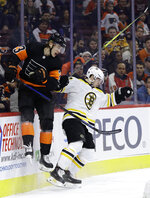 Philadelphia Flyers' Oskar Lindblom, left, collides with Boston Bruins' Torey Krug during the second period of an NHL hockey game, Wednesday, Jan. 16, 2019, in Philadelphia. (AP Photo/Matt Slocum)