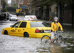 FILE - In this Aug. 28, 2011 file photo, a bicyclist makes his way past a stranded taxi on a flooded New York City street as Tropical Storm Irene passes through the city. Mayor Bill de Blasio is announcing a plan, Thursday, March 14, 2019, to protect lower Manhattan from rising sea levels by surrounding it with earthen berms and extending its shoreline by as much as 500 feet. (AP Photo/Peter Morgan, File)