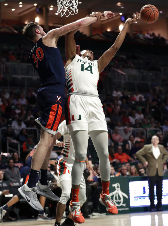 Virginia forward Jay Huff (30) and Miami center Rodney Miller Jr. (14) go for the ball during the first half of an NCAA college basketball game, Wednesday, March 4, 2020, in Coral Gables, Fla. (AP Photo/Lynne Sladky)