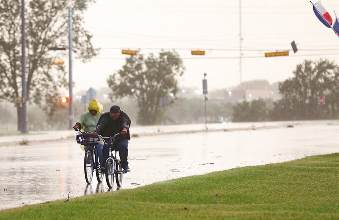 Cyclist make their way down a street in Bay City, Texas as Tropical Storm Nicholas approaches on Monday, Sept. 13, 2021. (Elizabeth Conley/Houston Chronicle via AP)