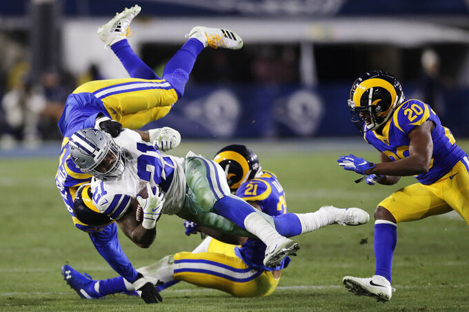 Dallas Cowboys running back Ezekiel Elliott is tackled by Los Angeles Rams linebacker Dante Fowler, top, and cornerback Aqib Talib during the second half in an NFL divisional football playoff game Saturday, Jan. 12, 2019, in Los Angeles. (AP Photo/Jae C. Hong)