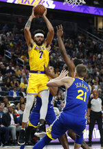 Los Angeles Lakers center JaVale McGee grabs a pass above Golden State Warriors defenders during the first half of an NBA preseason basketball game Wednesday, Oct. 10, 2018, in Las Vegas. (AP Photo/John Locher)