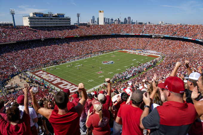 Oklahoma fans cheer in this overall view of the Cotton Bowl during the first half of an NCAA college football game against Texas, Saturday, Oct. 9, 2021, in Dallas. (AP Photo/Jeffrey McWhorter)