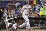 San Francisco Giants' Joe Panik watches his single during the fifth inning of a baseball game against the Miami Marlins, Wednesday, June 13, 2018, in Miami. At left is Marlins catcher J.T. Realmuto. (AP Photo/Lynne Sladky)