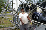Dale Williams, who cannot speak due to a tracheotomy from cancer, stands in front of his shrimp trawler that overturned and cracked during Hurricane Ida, in Plaquemines Parish, La., Monday, Sept. 13, 2021. Ida's Category 4 winds flipped Williams' trawler on its side, bending the frame and tearing nets, but it should be ready to go after about $1,500 in repairs, he said in an interview conducted by written notes. (AP Photo/Gerald Herbert)