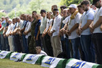 Mourners prepare for the funeral of newly identified victims at the memorial cemetery in Potocari near Srebrenica, Bosnia, Sunday, July 11, 2021. Bosnia is marking the 26th anniversary of the Srebrenica massacre, the only episode of its 1992-95 fratricidal war that has been declared a genocide by international and national courts. The brutal execution of more than 8,000 Muslim Bosniaks by Bosnian Serb troops is being commemorated by a series of events Sunday. (AP Photo/Darko Bandic)