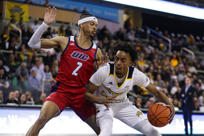 Northern Kentucky guard Jalen Tate (11) drives against Northern Kentucky guard Paul Djoko (2) during the first half of an NCAA college basketball game for the Horizon League men's tournament championship in Indianapolis, Tuesday, March 10, 2020. (AP Photo/Michael Conroy)