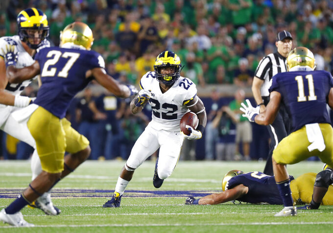 Michigan running back Karan Higdon (22) cuts between Notre Dame cornerback Julian Love (27) and safety Alohi Gilman (11) in the first half of an NCAA football game in South Bend, Ind., Saturday, Sept. 1, 2018. (AP Photo/Paul Sancya)