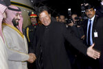 In this photo released by the Press Information Department, Pakistani Prime Minister Imran Khan, centre, greets Saudi Arabia's Crown Prince Mohammed bin Salman, left, upon his arrival at Nur Khan airbase in Rawalpindi, Pakistan, Sunday, Feb. 17, 2019.  Saudi Arabia's powerful Crown Prince Mohammed bin Salman began his four-day regional visit on Sunday, arriving in Pakistan where he is widely expected to sign agreements worth billions of dollars to help the Islamic nation overcome its financial crisis. (Press Information Department, via AP)