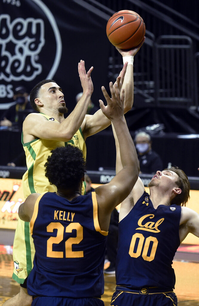 Oregon guard Chris Duarte (5) drives to the basket over California forward Andre Kelly (22) and guard Ryan Betley (00) during the second half of an NCAA college basketball game Thursday, Dec. 31, 2020, in Eugene, Ore. (AP Photo/Andy Nelson)