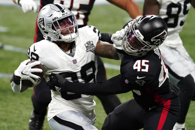 Las Vegas Raiders running back Josh Jacobs (28) stopped by Atlanta Falcons linebacker Deion Jones (45) denying a first down during the first half of an NFL football game, Sunday, Nov. 29, 2020, in Atlanta. (AP Photo/John Bazemore)