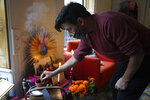 Sebastian Diaz Aguirre places incense in a Day of the Dead altar dedicated to his father, who died in a nursing home in Mexico last month, Wednesday , Oct. 28, 2020 in the Brooklyn borough of New York