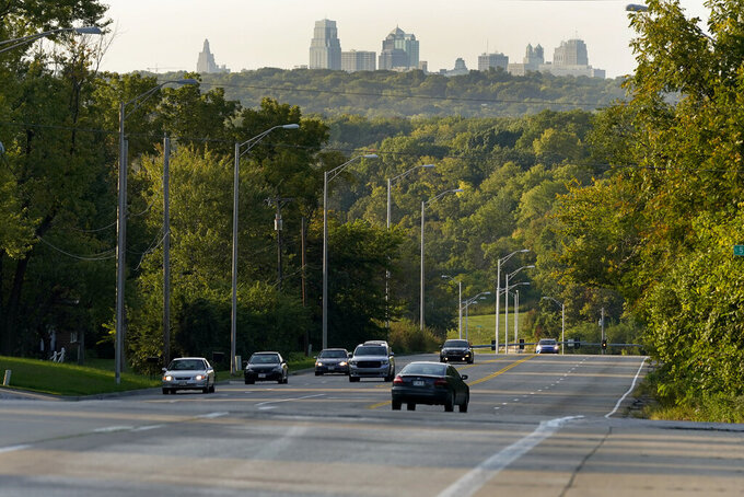 FILE - In this Sept. 24, 2020, file photo, cars travel on a stretch of Blue Parkway in Kansas City, Mo. After years of debate and a divisive election, Kansas City will soon have a street route named for Martin Luther King Jr., removing its designation as one of the largest city's in the U.S. to not have a street named for the civil rights icon. On Tuesday, April 13, 2021, the city's Board of Parks and Recreation approved a plan to name a 5-mile stretch that runs east to west for King, which includes Blue Parkway. (AP Photo/Charlie Riedel, File)