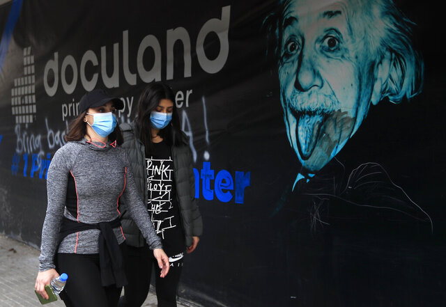 Lebanese women wear masks to help prevent the spread of the coronavirus, in Beirut, Lebanon, Wednesday, Jan. 27, 2021. Lebanon, a country of nearly 5 million and over 1 million refugees, is going through an unprecedented economic crisis that preceded the pandemic and restrictions imposed to combat it. (AP Photo/Hussein Malla)