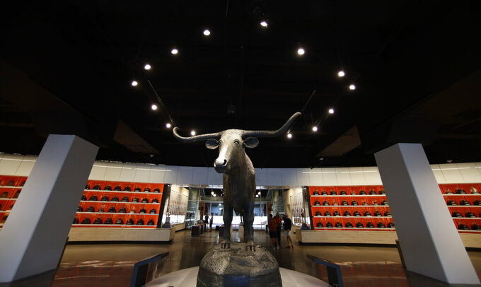 An 8-foot tall, 1,200-pound Longhorn statue greets visitors at the new Frank Denius Family University of Texas Athletics Hall of Fame, Friday, Aug. 30, 2019, in Austin, Texas. Displays honor all 55 of Texas' National Championship teams, 599 conference team titles, hundreds of individual national champions, 171 Olympians at 21 Olympiads, academic All-Americans and other scholastic honorees, as well as the traditions and tales that encompass the history of Longhorns. (AP Photo/Eric Gay)