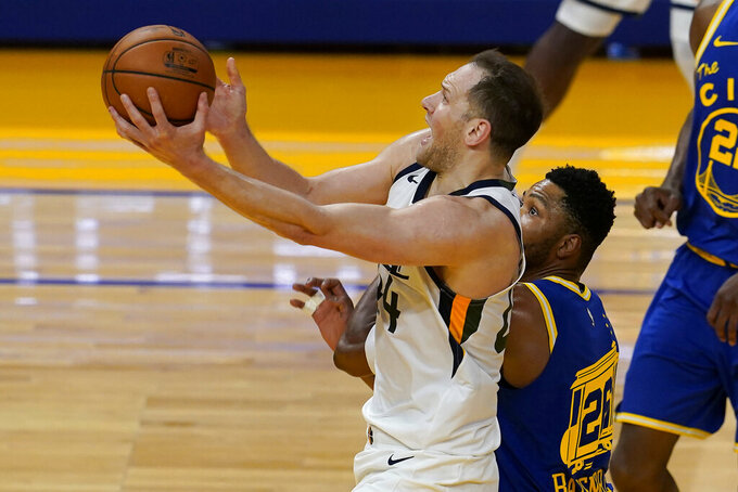 Utah Jazz forward Bojan Bogdanovic, left, shoots against Golden State Warriors forward Kent Bazemore during the first half of an NBA basketball game in San Francisco, Monday, May 10, 2021. (AP Photo/Jeff Chiu)
