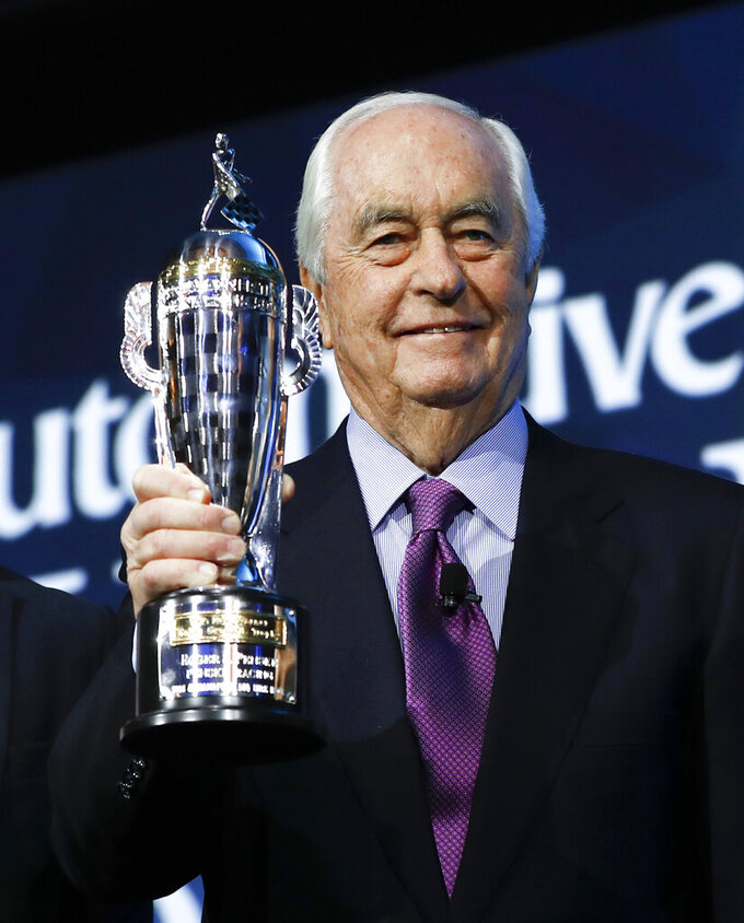 "FILE - In this Jan. 16, 2019, file photo, Roger Penske holds his ""Baby Borg"" trophy in Detroit. Joey Logano's win in Las Vegas was the fourth victory for one of Roger Penske's cars in seven days. It's quite the start to the year for Penske, who last month was inducted into NASCAR's Hall of Fame, feted at the Royal Automobile Club in Pall Mall, London and celebrated his 82nd birthday. (AP Photo/Paul Sancya, File)"