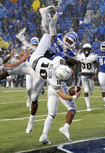 Central Florida quarterback McKenzie Milton (10) dives over Memphis defensive back Josh Perry (4) as he scores the go-ahead touchdown on a 7-yard run during the second half of an NCAA college football game Saturday, Oct. 13, 2018, in Memphis, Tenn. Central Florida won 31-30. (AP Photo/Mark Zaleski)