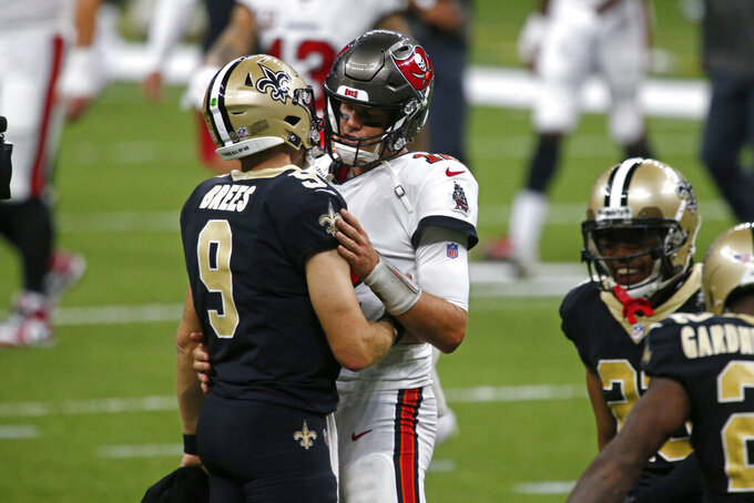 New Orleans Saints quarterback Drew Brees (9) and Tampa Bay Buccaneers quarterback Tom Brady hug after their season opening NFL football game in New Orleans, Sunday, Sept. 13, 2020. The Saints won 34-23. (AP Photo/Butch Dill)