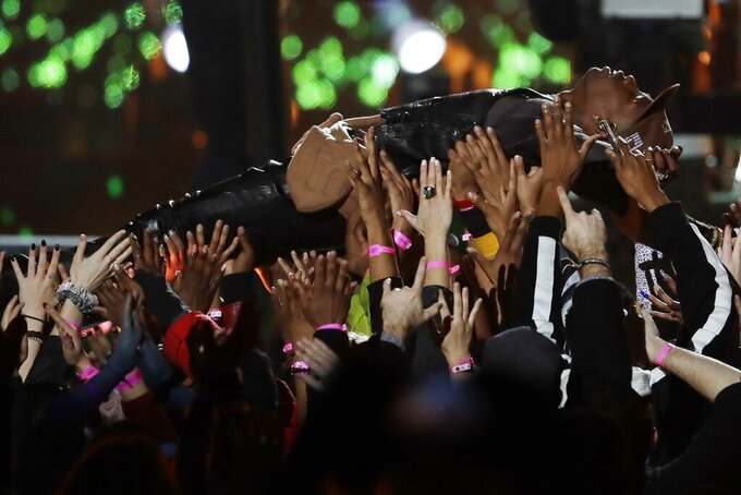 Travis Scott is carried by the crowd during halftime show of the NFL Super Bowl 53 football game between the Los Angeles Rams and the New England Patriots Sunday, Feb. 3, 2019, in Atlanta. (AP Photo/Jeff Roberson)
