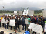 FILE - In this June 20, 2019 file photo Santa Anita Park workers hold a rally at the track in Arcadia, Calif. California Gov. Gavin Newsom signed a law, Wednesday June 26,2019 that would give the California Horsing Racing Board the authority to immediately suspend the license of Santa Anita. Thirty horses have died at the track in recent months. (AP Photo/Beth Harris,File)