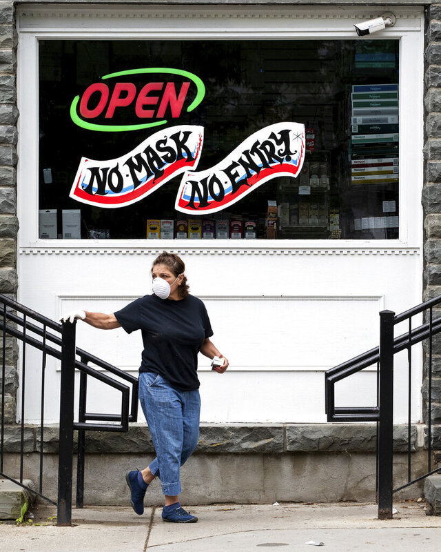 A woman wearing a mask and gloves exits The Shop, a convenience store in downtown Milford, Pa. on Thursday, May 28, 2020. Pike County is moving to Governor Tom Wolf's