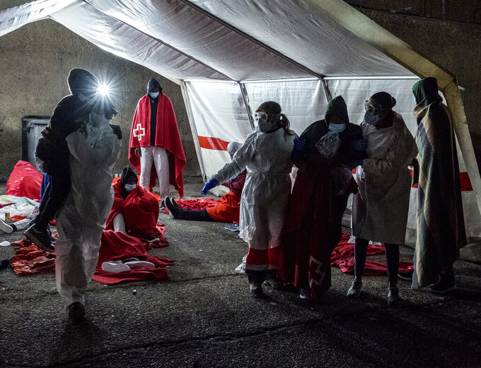 Rescued migrants try to make themselves comfortable inside a tent in the port of Arguineguin, Gran Canaria island, Spain, Saturday Jan. 16, 2021. A Spanish rescue ship rescued a boat 160 kilometres south of Gran Canaria with men, women and children on board in very poor condition. (AP Photo/Javier Bauluz)