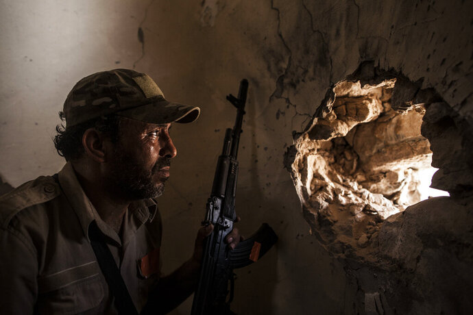 """FILE - In this Sept. 22, 2016, file photo, a fighter of the Libyan forces affiliated to the Tripoli government scans for targets from the minaret of a mosque in Sirte, Libya. The warring parties in Libya and their international backers — the United Arab Emirates, Russia and Jordan vs Turkey and Qatar — violated a U.N. arms embargo on the oil-rich north African country that remains """"totally ineffective,"""" U.N. experts said in a new report. (AP Photo/Manu Brabo, File)"""